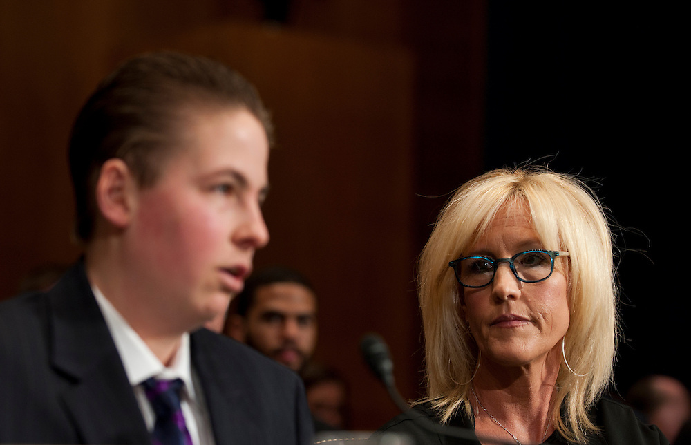 "Erin Brockovich listens as Trevor Schaefer, youth ambassador and founder of Trevor's Trek Foundation testifies during an Environment and Public Works Committee hearing on ""Disease Clusters and Environmental Health."""