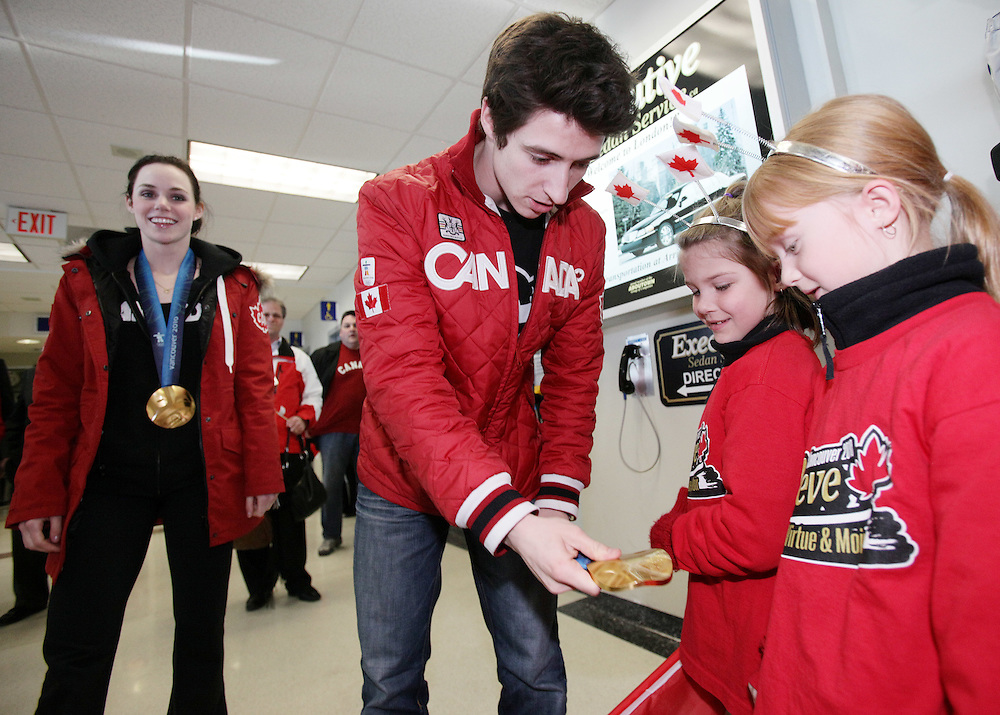 London, Ontario ---02/03/10--- Olympic Gold Medalist in Ice dance Scott Moir lets shows some young fans his gold medal as he and partner Tessa Virtue, left, arrive at the airport in London, Ontario, March 2, 2010.<br /> CP PHOTO/'GEOFF ROBINS