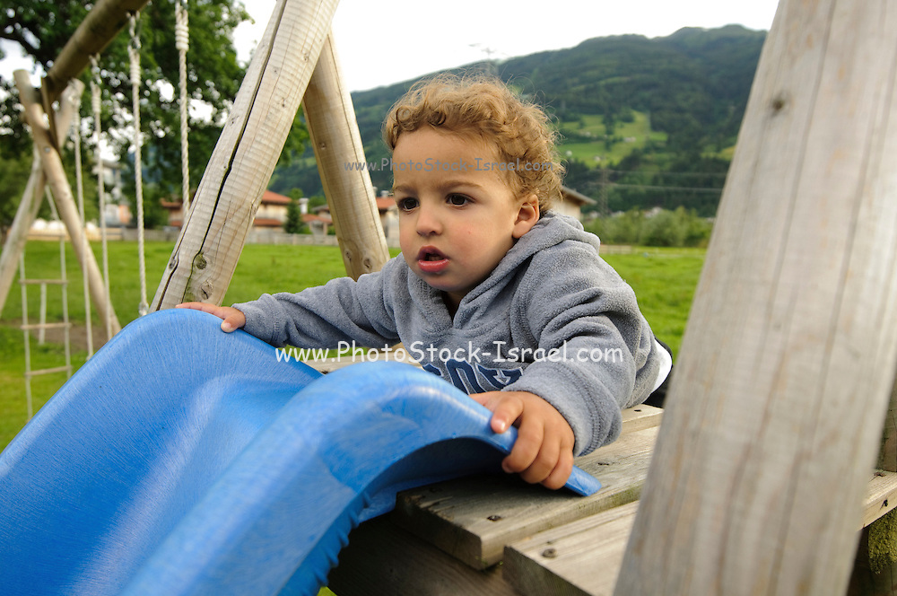 young child of two plays on a slide in a playground Photographed in Austria