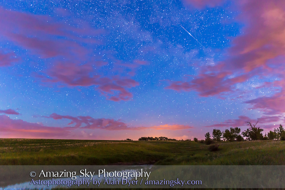 An iridium satellite flare, on the night of summer solstice eve, June 20, 2014, shot from home. This is a single exposure of 25 seconds, at f/2.8 and ISO 3200 with the Canon 16-35mm and Canon 6D. The sky is illuminated by perpetual twilight, the ground by distant lightning, and the clouds in part by light pollution from farm lights and highway lights.