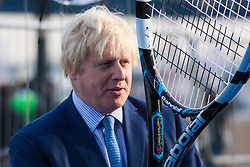 City Hall, London, November 24th 2014. Mayor Boris Johnsonwelcomes the world's best wheelchair tennis players with a game of mini tennis outside City Hall. The players are in London to compete in the NEC Wheelchair Tennis Masters 2014, being held at the Lee Valley Hockey and Tennis Centre, being held from 26 - 30 November. PICTURED: Mayor Boris Jognso holds a giant tennis raquet.
