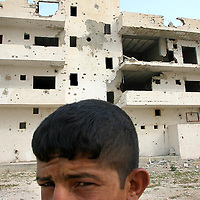 A Palestinian boy stands in front of a destroyed building by bullet impactc in Jericho. Photo by Olivier Fitoussi.