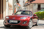 mazda mx-5 sportster red car in Kazimierz Dolny town in Poland Mazda MX-5 red sportster car in Kazimierz Dolny on Wisla river historic old town in Poland photography by Piotr Gesicki