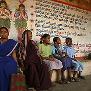 """A group of women and girls sit on a bench in Kokatnur, India. The mural behind them is part of an extensive public education campaign executed by MASS (a group of ex-Devadasis) and supported by its umbrella organization, MYRADA, and includes large painted murals around Yellamma temples with text and pictures warning against participating in the Devadasi system.  These murals depict scenes of various Devadasi dedication rituals with large """"X"""" marks through them.  While many of Yellamma's worshippers are illiterate, the paintings, with their vivid colors and the dramatic scenes they depict, are compelling.  Coupled with other forms of public education, the hope is that Devadasi dedications will become a thing of the past."""