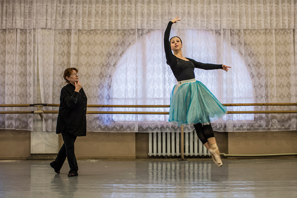 DONETSK, UKRAINE - FEBRUARY 1, 2015: Ballerina Tatiyana Ladiskaya leaps in the air as instructor Yelena Ogurtsova, left, looks on during a practice for the Donetsk National Academic Opera and Ballet Theatre in Donetsk, Ukraine. The opera company kicked off a new season in October, despite a separatist insurgency in Eastern Ukraine that has killed more than 5000 people. CREDIT: Brendan Hoffman for The New York Times