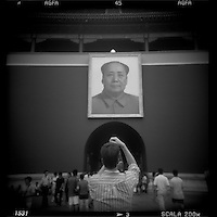 Asia, China, Beijing, Blurred black and white image of tourists taking snapshots in front of Chairman Mao Zedong above Gate of Heavenly Peace in the Forbidden City