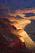 A bit of light breaks through the clouds to illuminate the rock walls of Grand Canyon National Park.