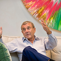 UK. London. Billionaire Hotel owner Sol Kerzner in his luxury home in Holland Park, West London. Behind him is a Damien Hirst painting..