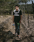 """Twenty-year-old Jesus Pineda Corona helping the search effort. His shirt reads: I will search for you until I find you."""""""