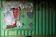 Peeling mural of golf club trolley on the side of green container parked near the European Space Agency's Kourou Spaceport.