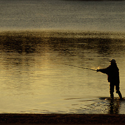 Man fishing early in the morning on a beach in Minneapolis
