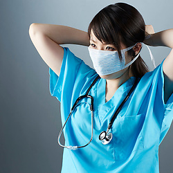 A portrait series representing the intense emotions that Doctors face.  A Japanese female Doctor wearing a white surgical mask, stethoscope, and blue medical scrub suit shown.