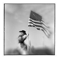 USA, Arizona, Taylor, Blurred black and white image of young rodeo queen holding American flag during Star Spangled Banner at July 4th rodeo celebration
