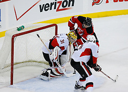 Jan 4, 2008; Newark, NJ, USA; Ottawa Senators goalie Alex Auld (31) makes a save on New Jersey Devils left wing Zach Parise (9) during the third period at the Prudential Center. The Devils defeated the Senators 4-3 in overtime.
