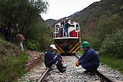 Passengers and train workers wait for the line to be cleared. During the rainy season, January to March, the route is heavily affected by landslides. Some can be cleared from the tracks in less than an hour while others force the tren macho to turn around and head back home.