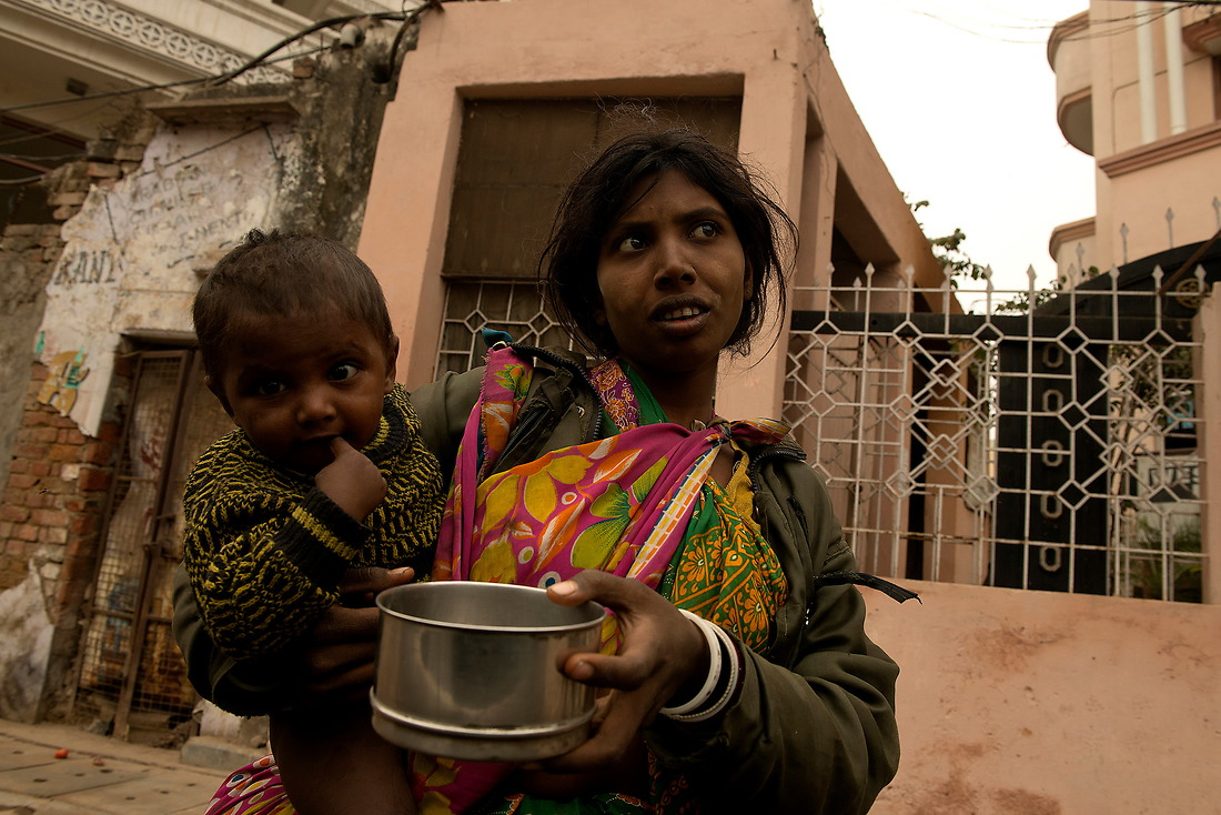 A woman and her child pan handles on February 2, 2013 in Varanasi, India. — © Jeremy Lock/