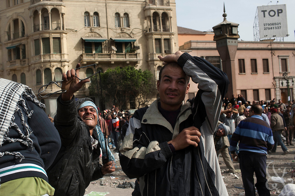 An Anti-Hosni Mubarak protester uses fires a sling-shot as others throw stones and bricksduring fighting with Mubarak supporters in the Tahrir square area February 03, 2011 in Cairo, Egypt. Protesters from both sides clashed throughout the day, throwing rocks and fighting at close range. . .Photo by Scott Nelson.