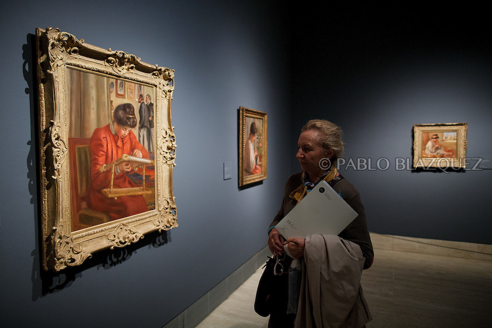 A member of the press looks at Pierre Auguste-Renoir's work 'Christine Lerolle Embroidering', painted in 1895-1898 at the Museum Thyssen-Bornemisza on October 17, 2016 in Madrid, Spain. 'Renoir: Intimacy' features 78 works by French painter Renoir (1841-1919) borrowed from museums and collections from around the world and will be open to the public from October 18, 2016 to January 22, 2017 (© Pablo Blazquez)