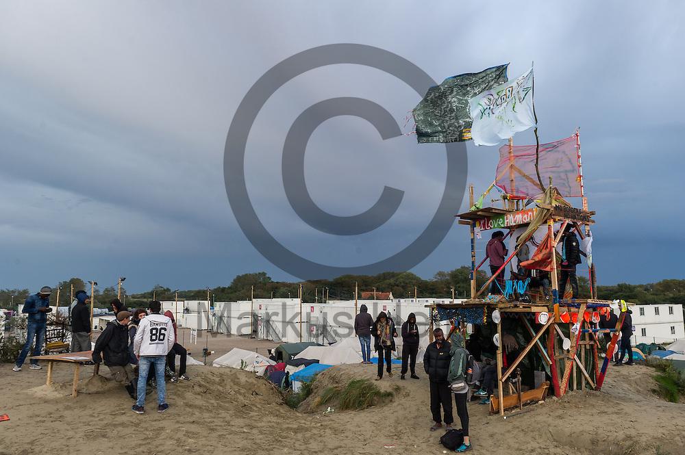 Calais, Frankreich - 16.10.2016<br /> Migranten stehen im Dschungel von Calais auf einem Sandberg neben einem Turm. Das Fluechtlingscamp an der Kueste zum Aermelkanal soll laut franz&ouml;sischer Regierung in den n&auml;chsten Tagen geraeumt werden. In dem Camp leben um die 1000 Fluechtlinge und warten auf die Moeglichkeit zur Weiterreise durch den Eurotunnel nach Gro&szlig;britannien. Photo: Foto: Markus Heine / heineimaging<br /> <br /> Calais, France - 2016/10/16<br /> Migrants stand in the Calais Jungle on a sandy mountain beside a tower.. The refugee camp on the coast to the English Channel is to be cleared in the next few days, according to the French government. In the camp live around the 1000 refugees and wait for the possibility to travel further through the Eurotunnel to the UK. Photo: Foto: Markus Heine / heineimaging<br /> <br /> ------------------------------<br /> <br /> Ver&ouml;ffentlichung nur mit Fotografennennung, sowie gegen Honorar und Belegexemplar.<br /> <br /> Bankverbindung:<br /> IBAN: DE65660908000004437497<br /> BIC CODE: GENODE61BBB<br /> Badische Beamten Bank Karlsruhe<br /> <br /> USt-IdNr: DE291853306<br /> <br /> Please note:<br /> All rights reserved! Don't publish without copyright!<br /> <br /> Stand: 10.2016<br /> <br /> ------------------------------