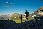 woman and young girl hike along ridge sillhouetted going to the sun mountain and reynolds mountain logan pass