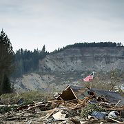 Rescuers remove a body as they search the massive debris pile after a mudslide destroyed dozens of homes and structures in the community of Oso, Wash. along the North Fork of the Stilliguamish River. The flag placed in the wreckage by residents, was discovered unsoiled in the debris pile.  Photographed on Monday, March 24, 2014 near Oso, Wash. (Joshua Trujillo, seattlepi.com)