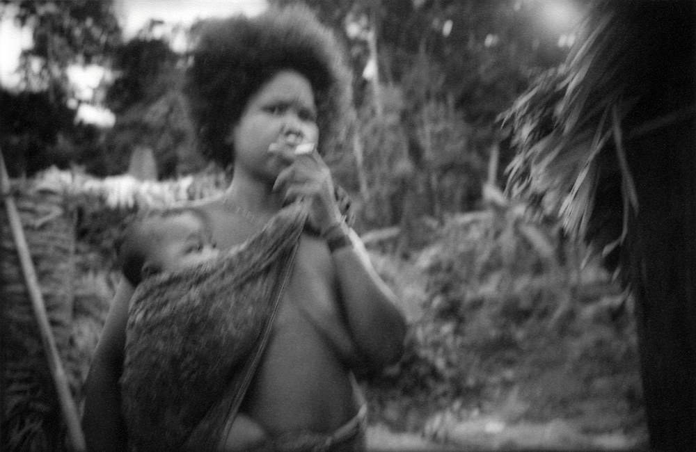 Death Throes of a Great Rainforest - Batek Negrito Mother smokes a clove cigarette and wearily eyes a stranger, Taman Negara National Park, Peninsular Malaysia.  Part of another failed gov't attempt to assimilate these Negrito hunter/gatherers this band of Batek occupy a compound on the edge of the rainforest set up by officials at the National Park.  The Batek soon dissolved back into the forest abandoning this settlement.