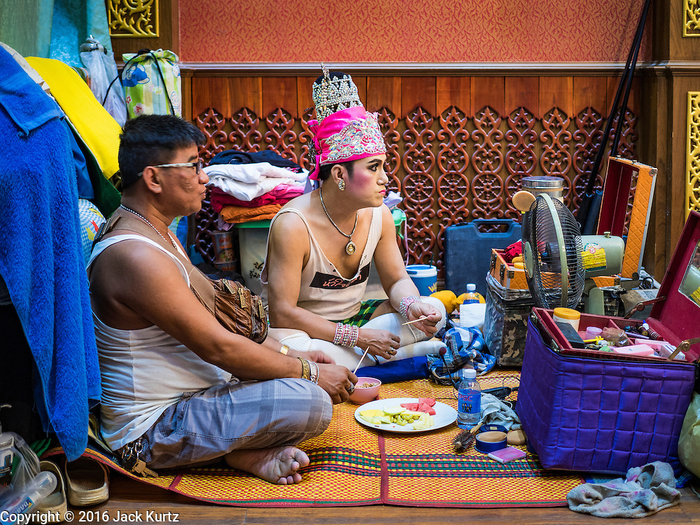 """30 JANUARY 2016 - NONTHABURI, NONTHABURI, THAILAND: Members of a """"likay"""" troupe snack and watch the """"likay"""" show at Wat Bua Khwan in Nonthaburi, north of Bangkok. Likay is a form of popular folk theatre that includes exposition, singing and dancing in Thailand. It uses a combination of extravagant costumes and minimally equipped stages. Intentionally vague storylines means performances rely on actors' skills of improvisation. Like better the known Chinese Opera, which it resembles, Likay is performed mostly at temple fairs and privately sponsored events, especially in rural areas. Likay operas are televised and there is a market for bootleg likay videos and live performance of likay is becoming more rare.     PHOTO BY JACK KURTZ"""