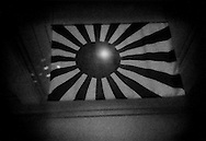 Japanese Hinomaru flag with radiating sun beams, the flag of the Imperial Japanese Army at Yushukan war museum on the grounds of Yasukuni War Shrine.  Tokyo, Japan.  Yasukuni War Shrine has become infamous to Japan's Asian neighbors because Class A war criminals are enshrined here along with rank and file soldiers, but, if there were any ethical ambiguity and Yasukuni, there is none in the apologist Yushukan War Museum, which glorifies Japan's actions during the Second World War / Pacific War, while whitewashing its more agregious crimes against humanity in China, Korean, and in Southeast Asia.