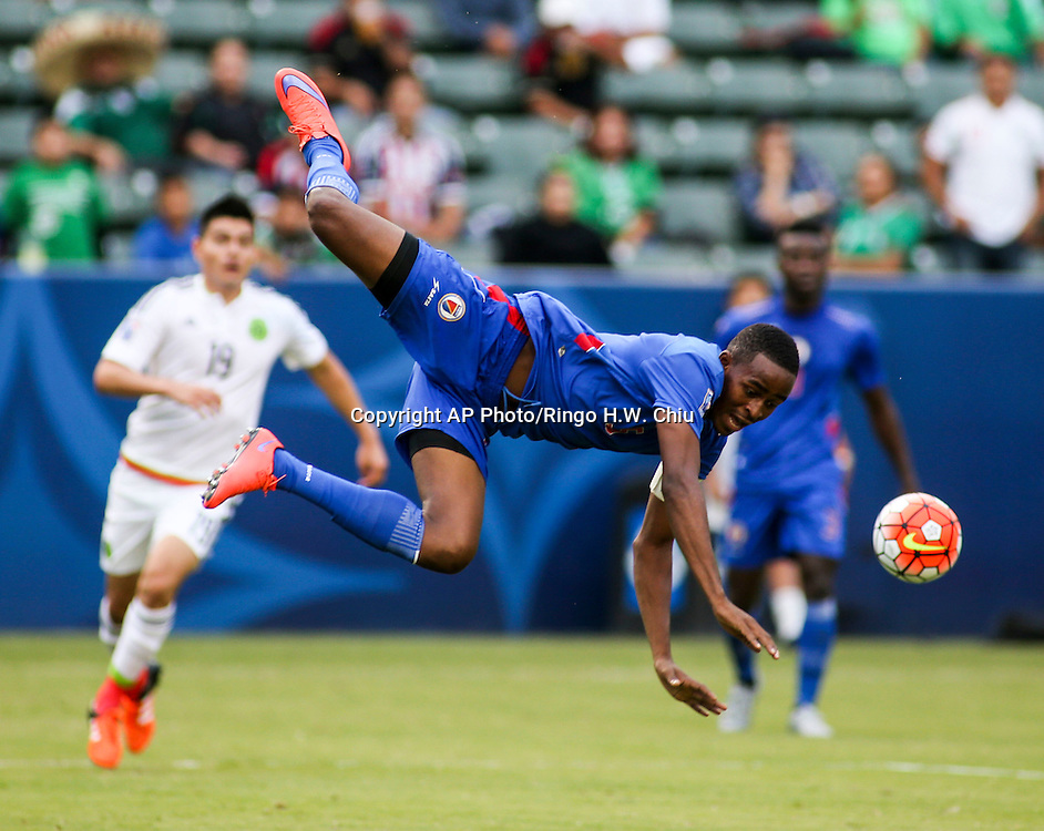 Haiti defender Jude Saint Louis flies over the ball against Mexico in the second half of a CONCACAF men's Olympic qualifying soccer match in Carson, Calif., Sunday, Oct. 4, 2015. Mexico won 1-0. (AP Photo/Ringo H.W. Chiu)
