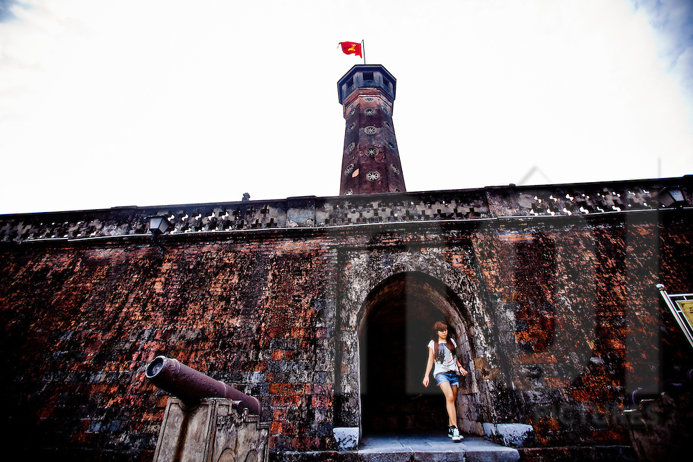 A young girl walks through the entrance to Cot Co flag tower in Hanoi, Vietnam.