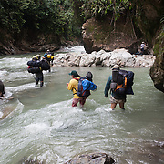 People cross a river on a trek into the reserve managed by their indigenous group
