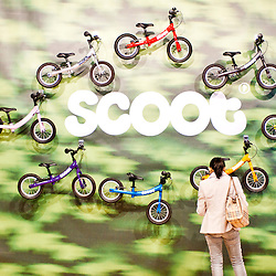 London, UK - 17 January 2013:  a visitor looks at baby bikes at the Scoot stand during the London Bike show 2013 at the Excel.