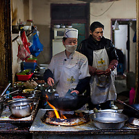 Cooking in an alleyway restaurant in Chengdu
