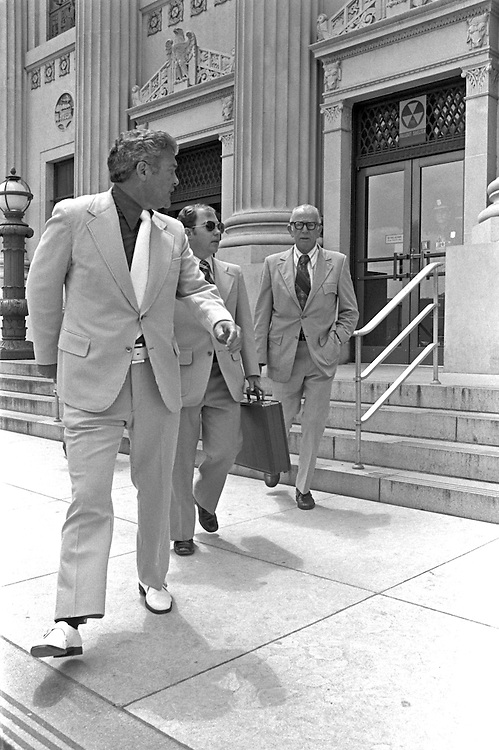 """Convicted of the murder of 102 VietNamese civilians  - the My Lai Massacre -  former U.S. Army Lieutenant William Calley (sunglasses) is escorted from the Fort Benning, Georgia confinement facility to a federal appeals court in nearby Columbus, Ga. At a later date, Calley's original sentence of life in prison was turned into an order of house arrest, but after three years, President Richard Nixon reduced his sentence with a presidential pardon -- Determine pricing and license this image, simply by clicking """"Add To Cart"""" below --"""