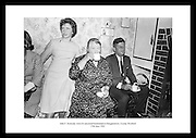 Picture shows President Kennedy sitting beside the fireside inside the homestead having a cup of tea.  On the left is Miss Josephine Ryan, daughter of Mrs. Ryan.  <br />
