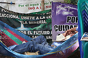 A man takes a nap at the La Puya resistance blockade after keeping watch all night. Since March 2nd, 2012, local neighbors from San José del Golfo and San Pedro Ayampuc have blocked the entrance to the EXMINGUA gold mine - owned by Kappes, Cassiday & Assocaites (KCA) based in Reno, Nevada, USA. Residents from the communities claim the industrial activity in their territories as illegal since they were not appropriately consulted before the mine began operating. La Puya, San Pedro Ayampuc, Guatemala. May 14, 2013.