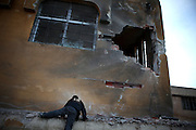 A boy climbs up to a hole in a local school building caused by rocket impact. On 22. February syrian army attacked the village of Courine, Province of Idlib, Syria. Courine was among the first villages in the northwest of Syria controlled by opposition. Some villagers and members of the defence units escaped to surrounding olive orchards when the attack begun in early morning. A majority of the inhabitants didn´t manage to escape. The heavy shelling lasts for 7 houres. Soldiers searched all houses, burnt some of them down, loot shops, stole cars and furniture. About 60 motorcycles were burnt down. Tanks demolished several houses. 6 men were executed, one child died of ahelling. A woman died as a result of an heart attack.