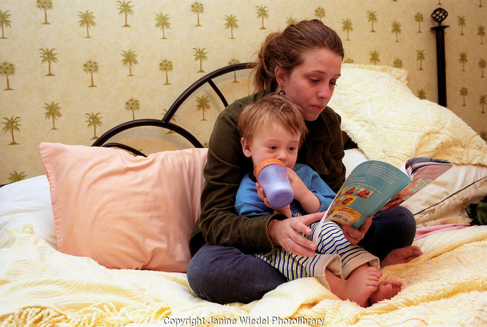 Young teenaged mother reading to her son at bedtime.