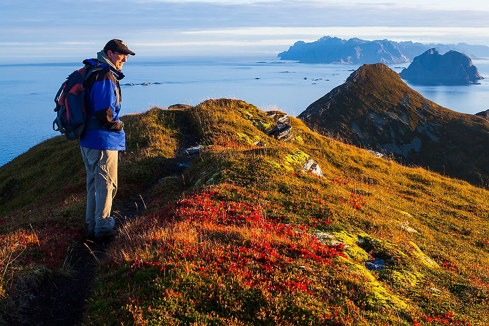 Parmenter Welty hikes a trail on the crest of Vaeroy Island, Lofoten Islands, Norway at sunrise. Mosken (right) and Moskenesoya Islands are visible in the distance.