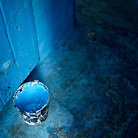 A blue bucket used to paint a door blue in a blue home in Chaouen, Morocco.