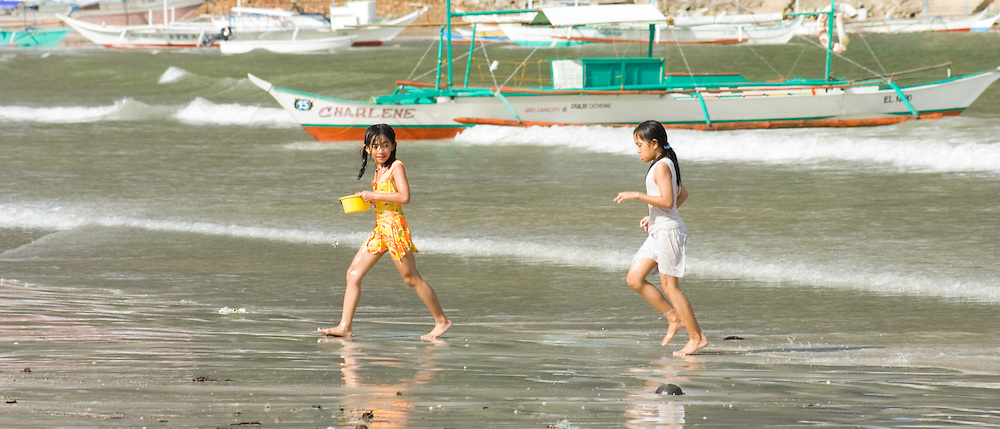 Young girls playing in the water with boats in the background, El Nido beach, Palawan, Philippines