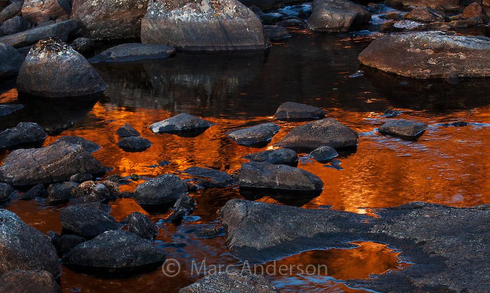 Warm light from the sun reflecting in a mountain stream, Gosaikunda, Nepal
