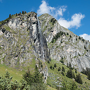 Waterfall above Fionnay, in the Pennine/Valais Alps, Switzerland, Europe. The dramatic Chamois Path (Sentier des Chamois) starts at La Chaux ski lift and ends at Fionnay PostBus. Cross Col Termin (2648m/8688 ft) in Haut Val de Bagnes nature reserve and descend to Lake Louvie via 1800s stone barns to the north, then to Fionnay (640 m up, 1415 m down in 8.5 hours).