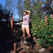 Woman Berry Picking in Garden with Dog