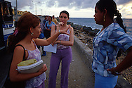 Un grupo de mujeres, papeles en mano uniformadas unas , otras no. Están reunidas conversando en el malecón.  A su lado un autobús estacionado como esperando para partir. Al fondo el cielo del atardecer. Cartagena de Indias,  2001 (Ramón Lepage / Orinoquiaphoto)     The fortified wall of Cartagena is in excellent condition and stretches more-or-less unbroken round a good portion of the Old Town. It is a pleasure for locals well as visitors to walk and observe the colonial architecture and excellent view of the Caribbean ocean..