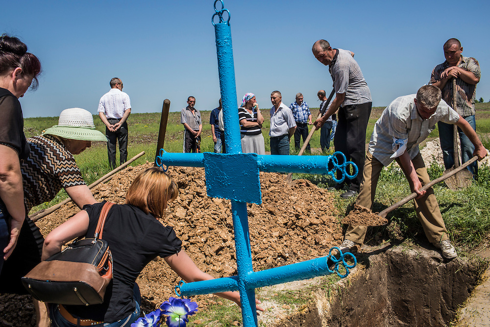 Mourners fill in the grave of Elena Ott, 42, on May 16, 2014 in Starovarvarovka, Ukraine. Ott was killed two days prior when the car she was riding in was fired on by forces her family believes to be the Ukrainian military.