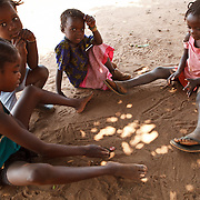 26 September 2011, Alges, Matala, Angola. Kids play a complicated game that involves the throwing of bottle caps and marking numbers in a grid in the sand. Canals leading of the Cunene river for irrigation purposes, becomes a lethal channel for the spread of cholera. Households close to the canal use the water for household purposes and open defecation near these water sources, lead to contamination later on. Villages who have erected water tanks and water suply directly to households, are generally protected from the spread of disease. Alges's water tanks supply 2,000 households (approximately 10,000 people).