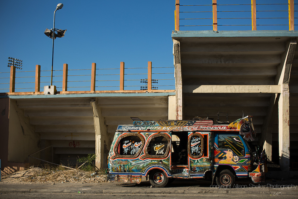 A taptap, one of the ubiquitous, unofficial city buses, sits in the parking lot of Sylvio Cator soccer stadium in downtown Port-au-Prince, Haiti, January 3, 2015. For months afterward, the stadium parking lot and field became home to many who were displaced by the 2010 quake.