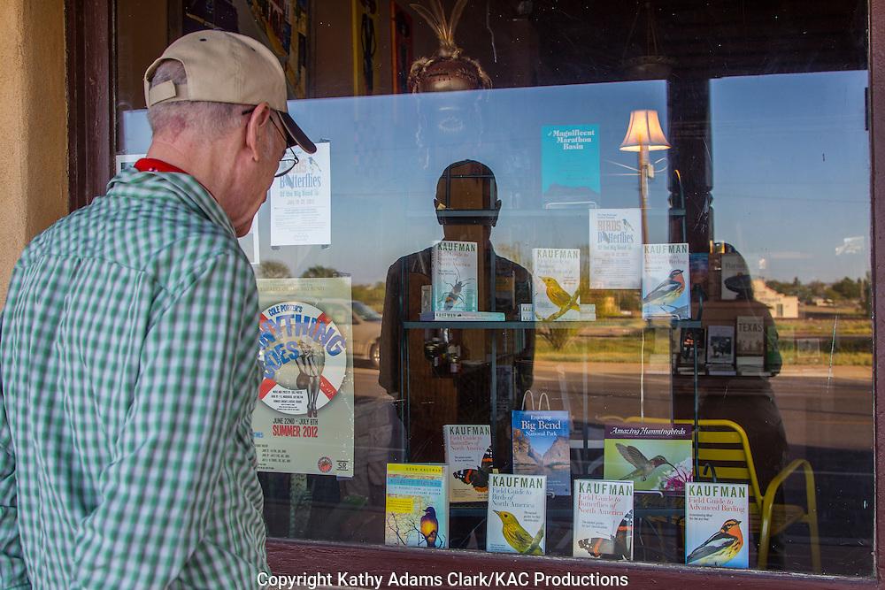 Gary Clark, Marathon, Texas, west Texas, looking in shop window at Enjoying Big Bend National Park and books by Kenn Kaufman.