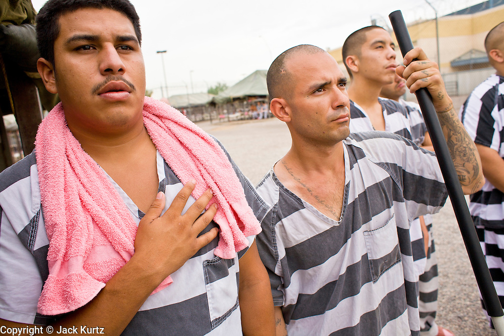 """17 JULY 2006 - PHOENIX, AZ: Inmates CHRISTIAN MIRANDA (LEFT), BERNIE VALENZUELA, and IRVING ORTIZ, stand with their hands over their hearts while the National Anthem is played in """"Tent City"""" in the Maricopa County Jail in Phoenix, AZ. There are about 650 inmates living in the tents. Maricopa County Sheriff Joe Arpaio recently started playing the Star Spangled Banner and God Bless America twice a day in the county jails. Inmates are encouraged, but not forced, to stand at attention with their hands over their hearts, when the music is played. When asked about the new policy Arpaio said, """"Our men and women are fighting and dying for our country in Iraq and that's the least these inmates can do."""" In 2011, the US Department of Justice issued a report highly critical of the Maricopa County Sheriff's Department and the jails. The DOJ said the Sheriff's Dept. engages in widespread discrimination against Latinos during traffic stops and immigration enforcement, violates the rights of Spanish speaking prisoners in the jails and retaliates against the Sheriff's political opponents.      PHOTO BY JACK KURTZ"""